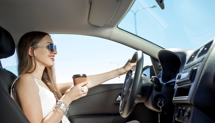 Woman drinking coffee in her car while driving.