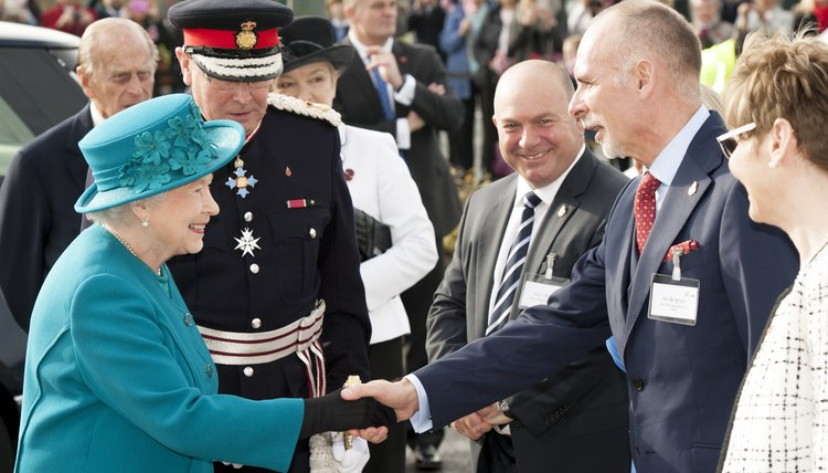 Queen Elizabeth smiles and shakes a man's hand.