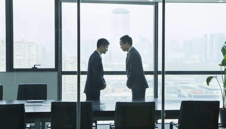 Two businessmen bowing towards each other as a greeting