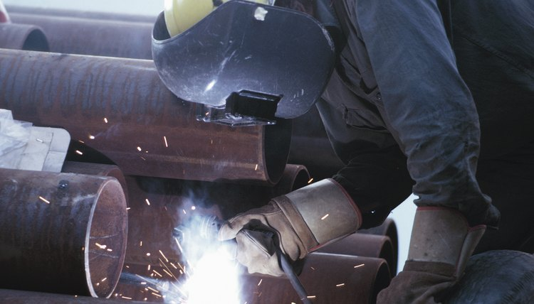 Welder working on pipes with torch