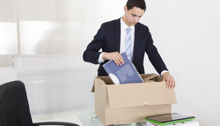 Businessman Packing Files In Cardboard Box In Office