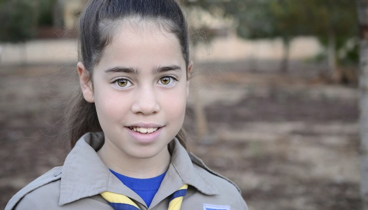 A young girl scout is on her way to camp.