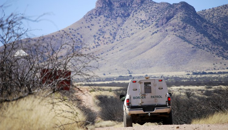 Border patrol truck driving on dirt road