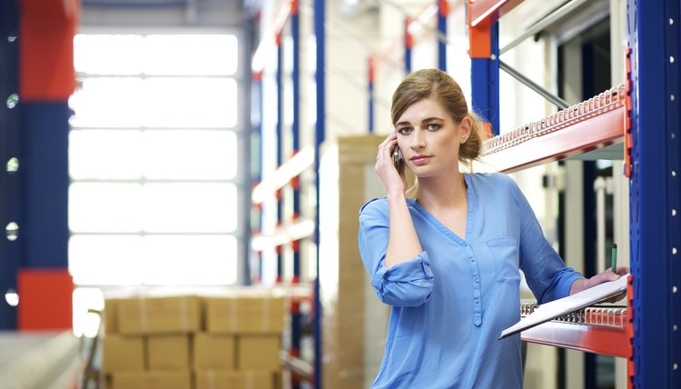 Female Logistics Worker On Mobile Phone In Warehouse
