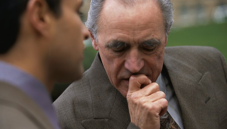 Older man having a serious talk with younger man outside.