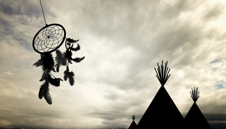 A dream catcher next to some teepees.