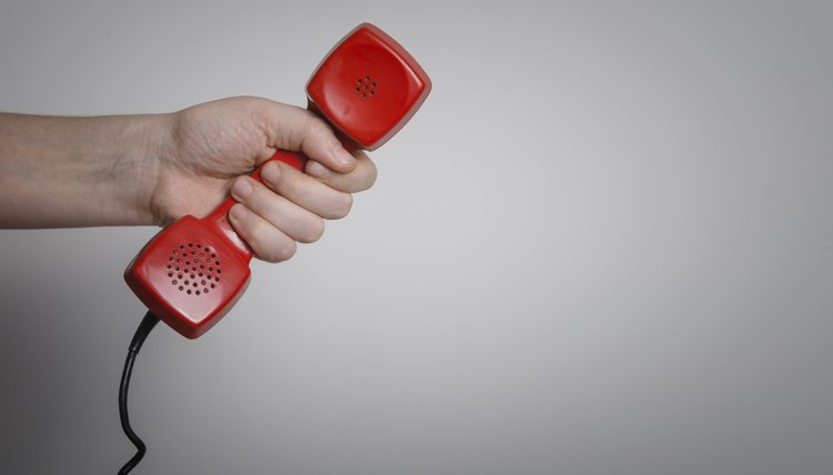 Hand holding red phone receiver