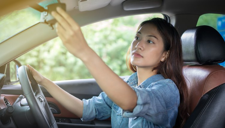 Asian women are adjusting the rear view mirror of the car