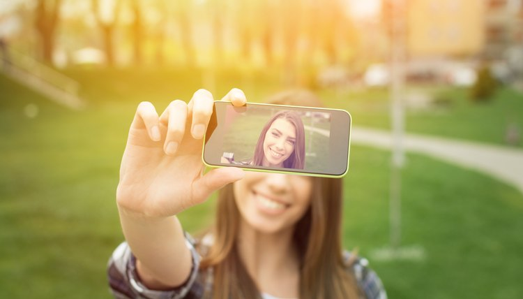 Young woman taking a selfie with phone