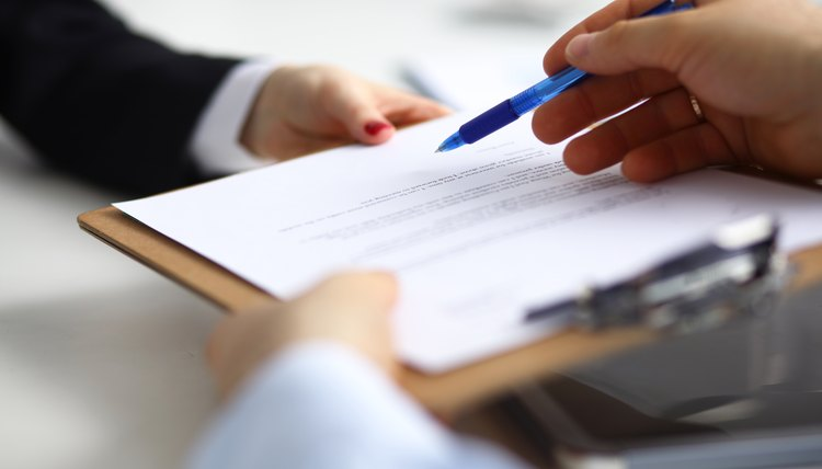 A lawyer hands his client a document to be signed and witnessed