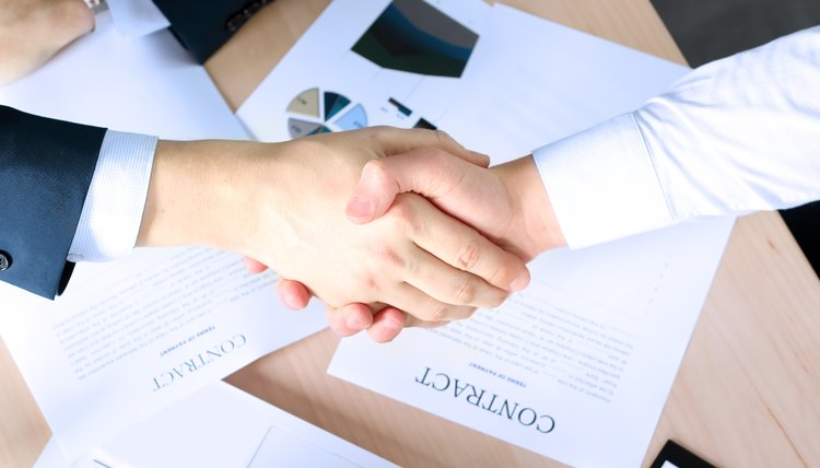 Firm handshake after signing a contract