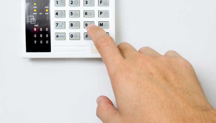 Man keys in code for home security alarm on white wall