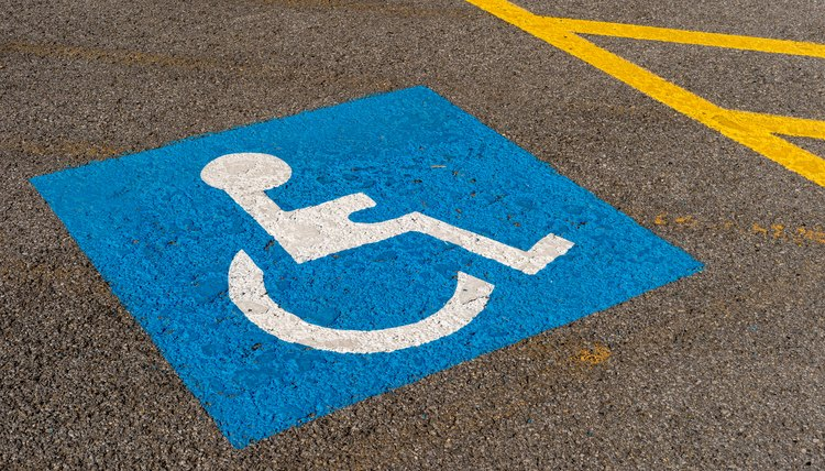 Disabled blue parking sign painted on asphalt
