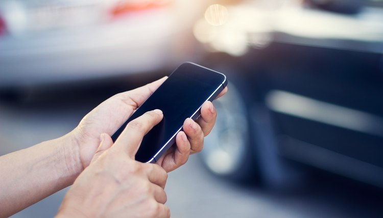 woman using smartphone at roadside after traffic accident