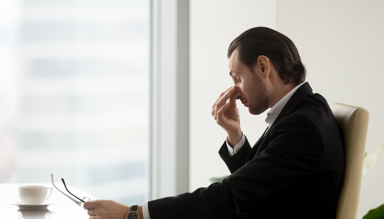 Man feels fatigue in eyes after work in office