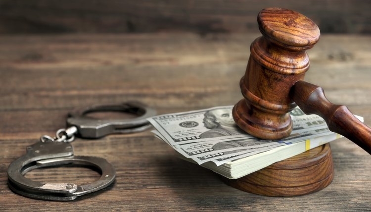 Cash bail, handcuffs and judge gavel on wood table