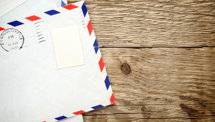 Envelope with postage on wooden surface