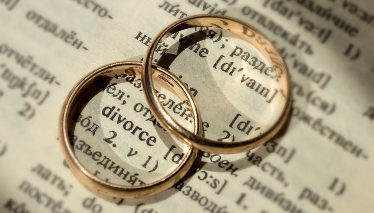 Two separate wedding rings next to the word 'divorce'. The concept of divorce, parting, infidelity . Selective focus.