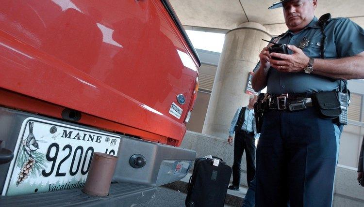 Police officer checks license plates on a car