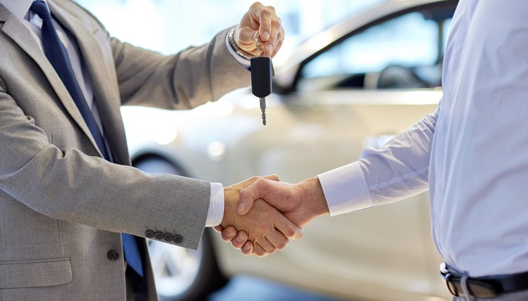 Man buying and receiving keys to a new car