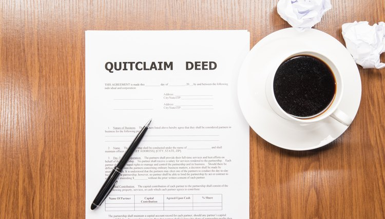 Quitclaim deed on wooden table with pen and cup of coffee