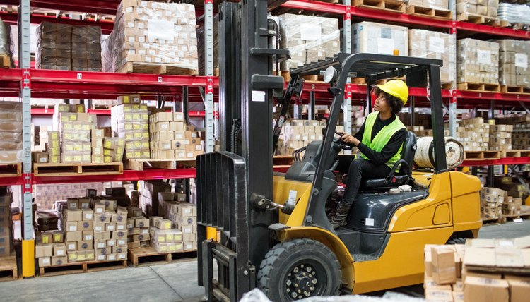 Woman driving forklift in warehouse