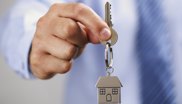 A man holding the key to a house