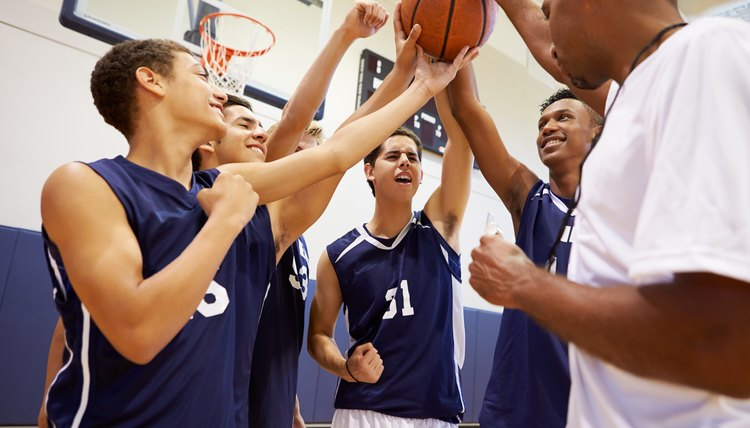 Male High School Basketball Team Having Team Talk With Coach
