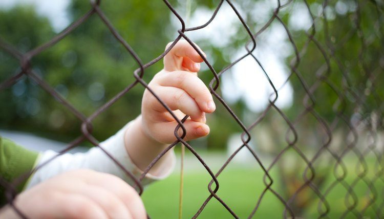 Child's hands on fence