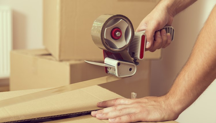 Man sealing moving boxes with tape