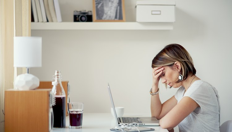 Upset woman working on a laptop in home office
