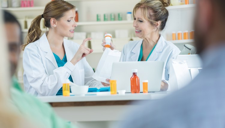 Confident female pharmacist gestures while talking with a colleague