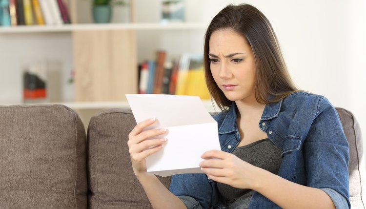 Worried woman reading a letter about her Series 7 License regarding aMisdemeanor