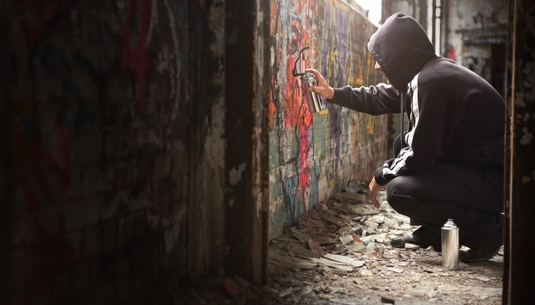 Teen spraying black paint on a graffiti wall
