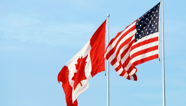 Canadian and American flags in the wind