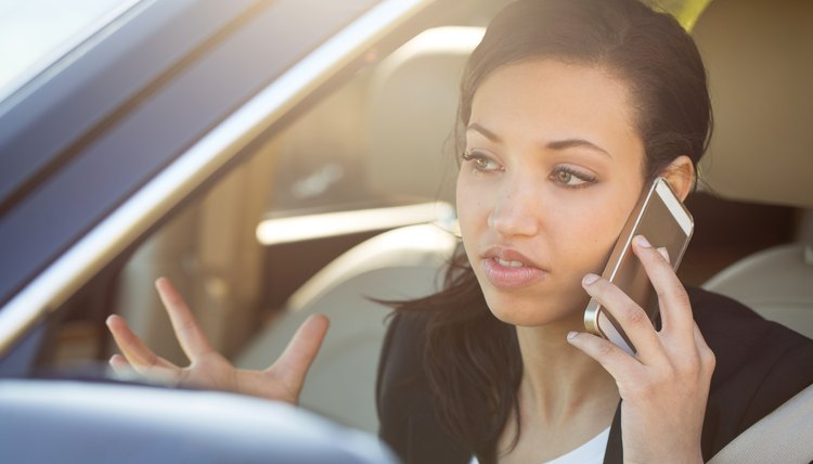 Woman calling 311 on cell phone from a parked car