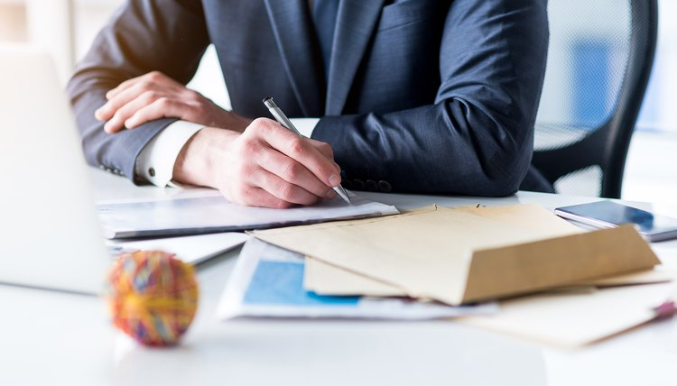 Man in an office writing a letter