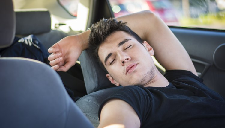 Young man sleeping inside his car, exhausted