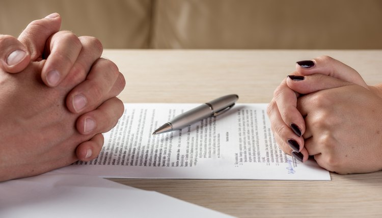 Hands of contractual parties, a woman and a man, signing a contract