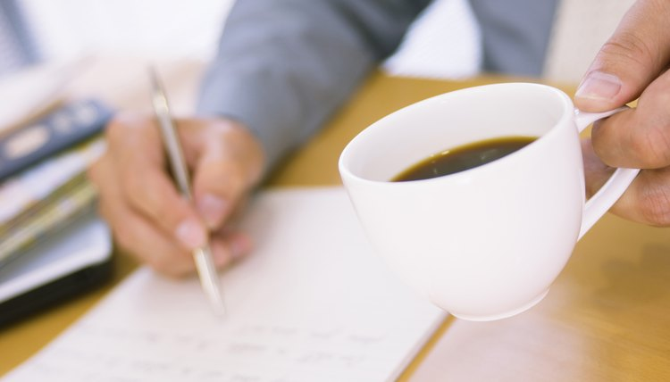 Man holding coffee, writing a letter