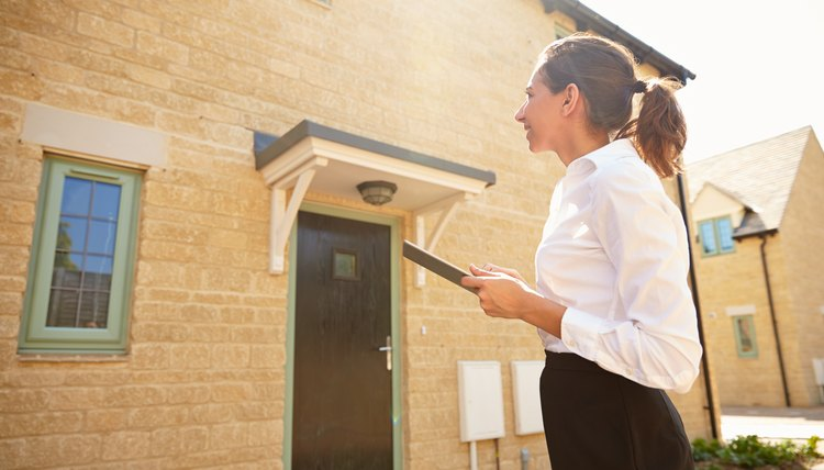 Female real estate agent looking at a house exterior