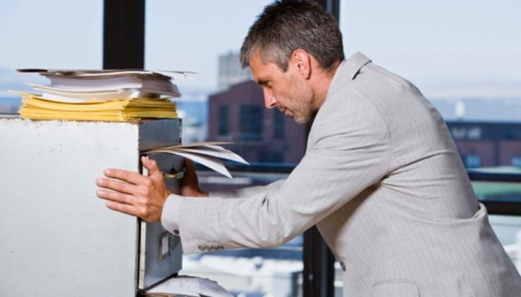 Man holds an overflowing file cabinet