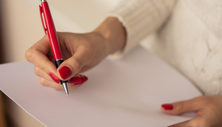 Woman writing on blank paper with a pen