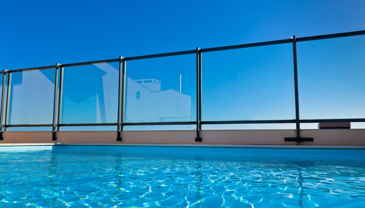 A swimming pool with a glass fence on a sunny day