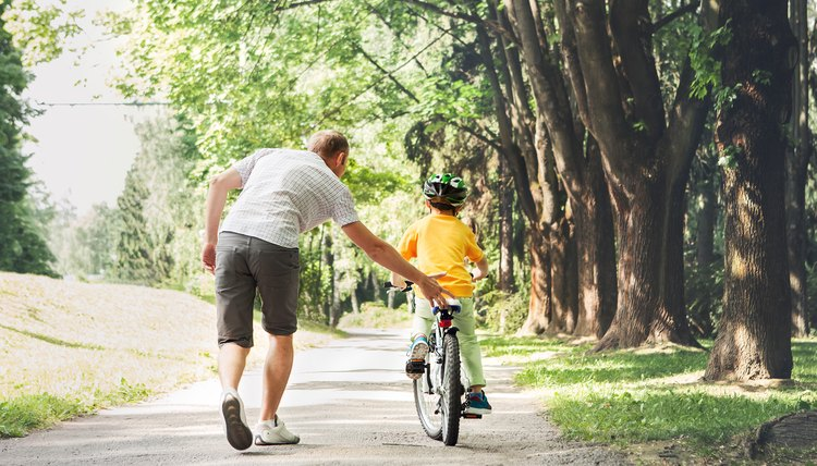 Father teaching his  stepson to ride a bicycle