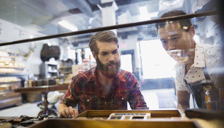 Men browsing pocketknives in display case in shop