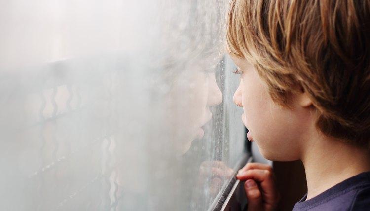 Little boy looking through the window
