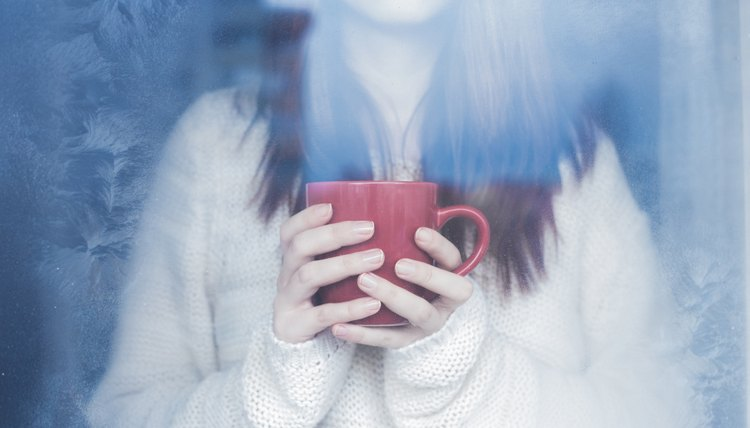 Woman holding mug of tea looking out the window