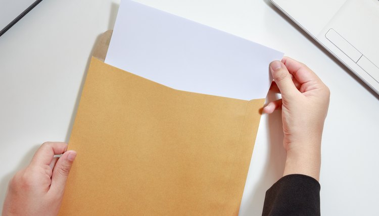 Hands taking a summons notice out of an envelope