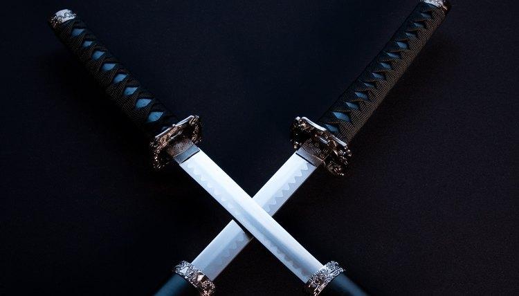 Crossed blades, katana and wakizashi on black background.